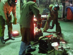 Molten Bronze Poured from the Crucible into the Two-Part Sand Mold